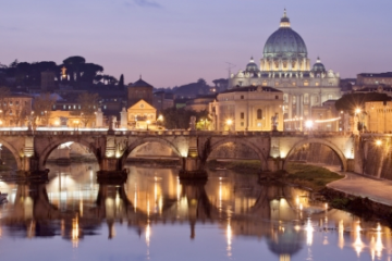 Image of St. Peter's Basilica across the Tiber river at night.